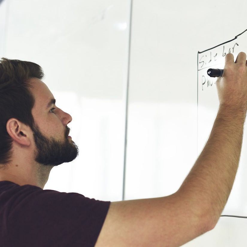 Picture of a man writing on a whiteboard