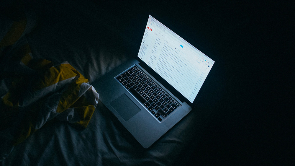 Picture of a laptop at night time with screen glare