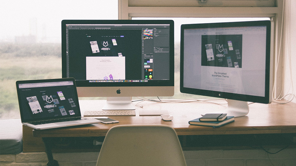 Picture of a desk with 3 computer monitors