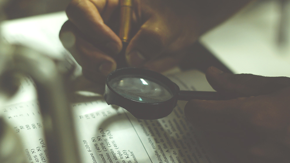 Picture of a magnifying glass looking at a sheet of paper