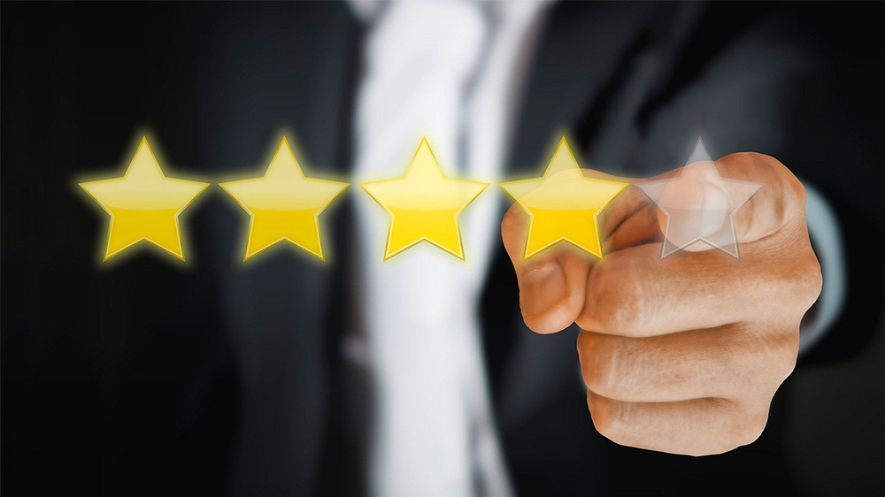 Picture of a person pointing to 5 review stars